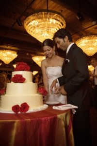 Bride and Groom Cut the Cake with Chandeliers in Background Ballroom